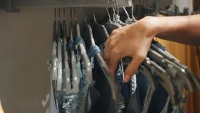 Женские руки смотрят через одежды вися на вешалках в магазине одежды видеоматериал