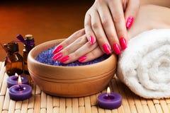 Женские руки с ароматичными свечами и полотенцем. Спа Стоковое Изображение