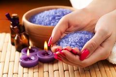 Женские руки с ароматичными свечками и полотенцем. Спа Стоковая Фотография