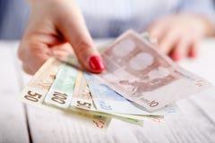 Женские руки с банкнотами дают деньги Стоковое Фото