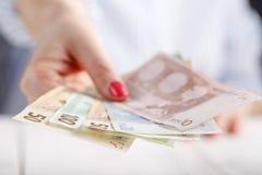 Женские руки с банкнотами дают деньги Стоковые Изображения