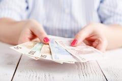 Женские руки с банкнотами дают деньги Стоковое фото RF