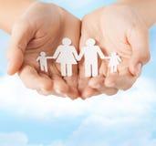 Женские руки с бумажной семьей человека Стоковая Фотография RF