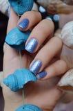 Женские руки с голубым дизайном ногтя яркого блеска Стоковая Фотография RF