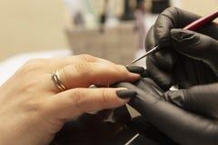 Женские руки с красивым маникюром, мастером в ногтях политур салона стоковые изображения