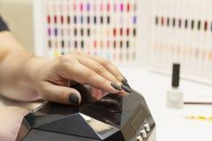 Женские руки с красивым маникюром, мастером в ногтях политур салона стоковая фотография rf