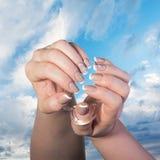Женские руки с классическим французским маникюром держат стеклянную чашку против голубого неба Стоковое Изображение