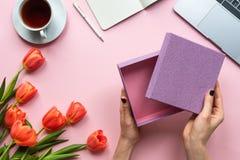 Женские руки с открытой пустой коробкой на розовой предпосылке Предпосылка с чаем, ноутбуком и цветками стоковые изображения rf