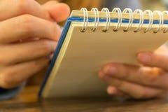 Женские руки с сочинительством ручки на тетради Стоковые Фотографии RF