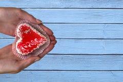 Женские руки с тортом сердца форменным на предпосылке старой деревянной текстуры стоковое фото