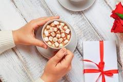 Женские руки с чашкой горячего какао с зефирами, подарочной коробки, роз на белизне Стоковое Изображение