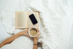 Женские руки с чашкой кофе, телефоном и старой книгой Стоковые Изображения RF