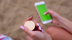 Женские руки с bitcoin и мобильным телефоном акции видеоматериалы