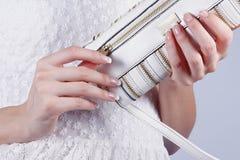 Женские руки с manicure с сумкой стоковая фотография rf