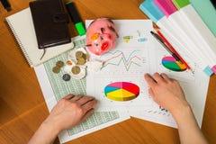 Женские руки, тетради, копилка и деньги, карандаш, ручка, метка Стоковые Изображения RF