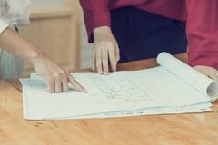 Женские руки указывая на чертеж плана дома стоковая фотография