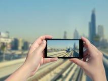 Женские руки ` s фотографируют монорельс и небоскребы Дубай на мобильном телефоне Изображение дороги метро и метро тренируют на d Стоковое Изображение