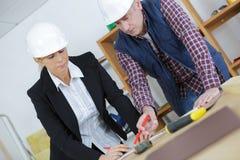 Женские светокопии архитектора и мастера рассматривая в офисе Стоковая Фотография