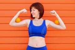 Женские сила, свежесть и здоровье: женщина пригонки в голубом бюстгальтере спорт стоя и проверяя мышцы с 2 апельсинами на ее бице стоковая фотография rf