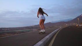 Женские скейтбордисты на предпосылке неба захода солнца в съемке steadicam замедленного движения Ехать гора на доске сток-видео