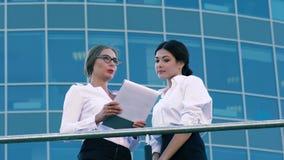 Женские сотрудники обсуждая их сотрудничество дела акции видеоматериалы