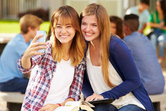Женские студенты средней школы принимая Selfie на кампусе Стоковые Изображения