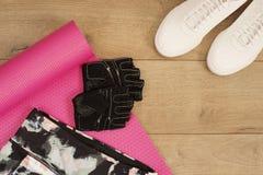 Женские тапки, ботинки спорта, гетры и перчатки тренировки в стиле положения квартиры, взгляд сверху Тренеры моды ультрамодные, к Стоковое Фото