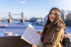 Женские туристские взгляды на карте улицы перед мостом башни, Великобританией стоковая фотография rf