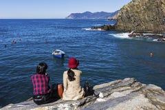 Женские туристы сидя на утесе в Riomaggiore в Италии Стоковые Изображения RF