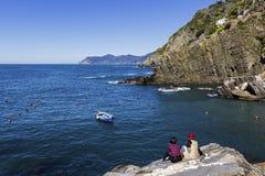 Женские туристы сидя на утесе в Riomaggiore в Италии Стоковое фото RF