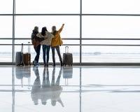 Женские туристы смотря самолеты через окно Стоковая Фотография