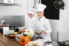 Женские шеф-повара подготавливая еду на кухне ресторана Стоковые Фотографии RF