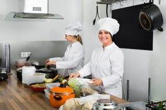 Женские шеф-повара подготавливая еду на кухне ресторана Стоковые Фото