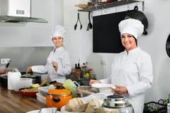 Женские шеф-повара подготавливая еду на кухне ресторана Стоковая Фотография RF
