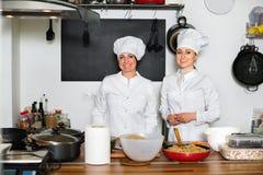 Женские шеф-повара подготавливая еду на кухне ресторана Стоковые Изображения RF