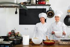 Женские шеф-повара подготавливая еду на кухне ресторана Стоковое фото RF