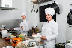 Женские шеф-повара подготавливая еду на кухне ресторана Стоковая Фотография