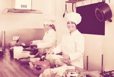 Женские шеф-повара подготавливая еду на кухне ресторана Стоковое Изображение RF