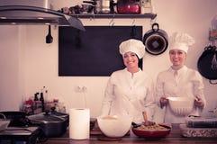 Женские шеф-повара подготавливая еду на кухне ресторана Стоковое Изображение