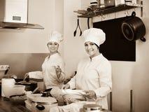Женские шеф-повара подготавливая еду на кухне ресторана Стоковое Фото