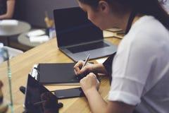 Женские waitres писать отчет используя информацию от компьтер-книжки с насмешкой вверх по экрану стоковая фотография rf