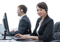 Женский агент обслуживаний клиента при шлемофон работая в центре телефонного обслуживания Стоковое фото RF