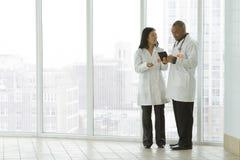 Женский азиатский доктор с Афро-американским доктором с таблеткой стоковые фотографии rf
