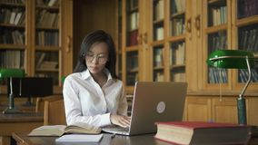 Женский азиатский студент сидя на таблице с зеленой лампой видеоматериал
