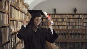 Женский азиатский юрист студента в стеклах roung и черном удерживании мантии акции видеоматериалы