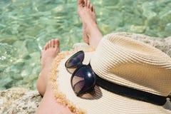 Женский аксессуар, sunhat соломы, стекла и длинные ноги очистьте море каникула территории лета katya krasnodar конец вверх стоковое фото