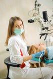 Женский дантист обрабатывая костоеду используя микроскоп на офисе дантиста Стоковая Фотография