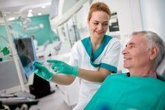 Женский дантист показывая зубоврачебный рентгеновский снимок к пациенту Стоковое Изображение