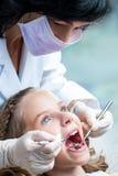 Женский дантист работая на зубах детей стоковые фотографии rf