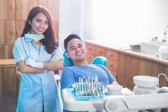 Женский дантист с счастливым мужским пациентом на клинике стоковое фото